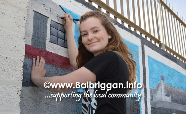 Artist Lauryn Flynn painting the beach mural